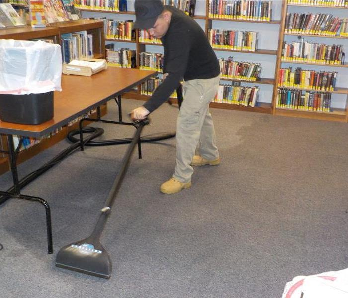 technician extracting water from wet carpet